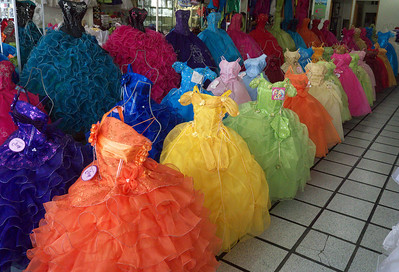 "June 2012 Mazatlán Dress shop catering to Quinceañera (One (f.) who is fifteen), girl's coming out party celebrated on her 15th birthday. The dresses in foreground are for younger girls, but I have not found out what that special occasion is.  from Wiki In Mexico, the birthday girl, known as the Quinceañera, is made-up with elegant makeup. Traditionally, this would be the first time she was to wear makeup, however this is usually no longer the case. The Quinceañera is also expected to wear a formal evening dress. Traditionally, the dress worn by the Quinceañera to this event is an evening ball gown.  In the Mexican tradition - considering the teenager is Catholic - the Quinceañera celebration begins with a Thanksgiving mass. For this mass, the teenager wears a formal dress. Conventionally, the Quinceañera wore a pink dress to symbolize her purity; however, in recent decades, white has become the preferred color (carey.... they seem to have strayed from the colour theme). If the Quinceañera chooses, she may wear a white dress with personalized touches, including embroidery, pearls, sequins, or any other adjustment that would best reflect her sense of fashion. She arrives to the celebration accompanied by her parents, godparents, and court of honor. The court of honor is a court of her chosen peers made up of paired off girls and boys, respectively known as ""damas"" and ""chambelanes."" Typically, there are fourteen or seven pairs ""damas"" and ""chambelanes,"" which each literally translate to dames and chamberlains. At this religious mass, a rosary, or sometimes a necklace with a locket or pendant depicting the image of Mexico's patron saint the Virgin of Guadalupe, is awarded to the teenager by her godparents, such necklace having been previously blessed by the church clergy. She is also awarded a tiara. The symbolism behind the tiara is to serve as a reminder that to her loved ones, especially her immediate family, the Quinceañera will always be a princess, however some also see it as denoting she is a ""princess"" before God and the world. After this, the girl may leave her bouquet of flowers on the altar for the Virgin Mary.  After the Thanksgiving mass, guests gather for a reception where the remaining celebratory events meant to honor the Quinceañera will take place, including the rendering of gifts. This reception may be held at the Quinceañera's home, at an events room, such as a dining hall, banquet hall, or casino, or in some cases publicly held, similar to a block party. During the reception, the birthday girl usually dances a traditional waltz with her ""Chambelan de Honor,"" which is her chosen escort, and her court of honor. Many times this section of the celebration is previously practiced and/or choreographed, oftentimes weeks in advance, sometimes even with months of anticipation. The basic reception generally consists of six major parts, with dances taking place while a traditional Mexican entree meal is served:      The formal entry - A grand entrance by the Quinceañera made once most guests have been seated.     The formal toast - An optional but usual part of the reception generally initiated by the parents or godparents of the birthday girl.     The first dance - Usually a waltz where the girl dances starting with her father.     The family dance - Usually a waltz involving just the immediate relatives, the ""chambelanes"", the godparents, and the closest friends of the girl.     The preferred song - Any modern song particularly preferred by the Quinceañera is played and danced.     The general dance - Also usually a waltz, where everyone dances to a musical waltz tune.  Traditionally, Mexican girls could not dance in public until they turned fifteen, except at school dances or at family events. Therefore, the Quincenera's waltz with the chamberlanes is the girl's first public dance ever.  Some families may choose to add ceremonial components to the celebration, depending on local customs, such as the ceremony of the Change of Shoes, in which a family member slips the Quinceañera with her first high heel shoes; the Crowning ceremony, in which a close relative vests her with a crown on her head, and ""Ceremonia de la Ultima Muñeca"" (the Ceremony of the Last Doll), during which her father presents her with a doll usually wearing a similar dress as the Quinceañera herself. ( carey... also available in the dress shop). The Ceremony of the Last Doll is based on a Maya tradition and it is related to the birthday girl's receipt and renouncement of the doll as she grows into womanhood. Likewise, the ceremony of the change of shoes symbolizes the girl's passage into maturity.  Once all symbolic gestures have taken place, the dinner is commenced. At this point, the celebration reaches its high point: contracted musical groups begin playing music, keeping the guests entertained. The music is played while the guests dine, chat, mingle, and dance.  The next morning the family and closest friends may also attend a special breakfast, especially if they are staying with the family. Sometimes what is known as a recalentado (re-warming) takes place, in which any food not consumed during the event of the night before is warmed again, for a brunch type event."